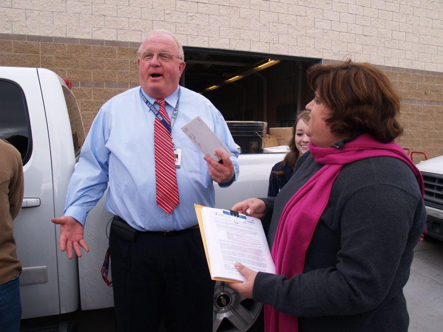 Principal+Robert+Gerye+accepts+checks+from+community+volunteers.